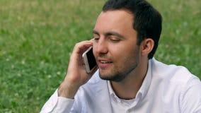 Ένας νέος εργαζόμενος γραφείων μιλά στο τηλέφωνο κυττάρων στο πάρκο πόλεων Στοκ Εικόνες