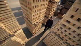 Ένας νέος εργαζόμενος στους ομοιόμορφους περιπάτους μεταξύ των ξύλινων παλετών στην υπαίθρια αποθήκη εμπορευμάτων διανομής o E απόθεμα βίντεο