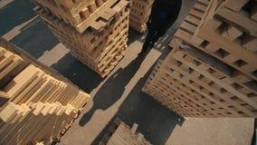 Ένας νέος εργαζόμενος στους ομοιόμορφους περιπάτους μεταξύ των ξύλινων παλετών στην υπαίθρια αποθήκη εμπορευμάτων διανομής o E φιλμ μικρού μήκους