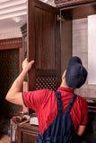 Ένας νέος εργαζόμενος συγκεντρώνει τα σύγχρονα ξύλινα έπιπλα κουζινών στοκ φωτογραφία