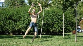 Ένας νέος ευτυχής τύπος με ένα γυμνό σύγχρονο μπαλέτο χορού κορμών και σε ένα θερινό πάρκο Αργός-Mo απόθεμα βίντεο