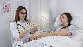 Ένας νέος θηλυκός γιατρός προετοιμάζει μια σύριγγα για την έγχυση Θεραπεία του ασθενή στο νοσοκομείο φιλμ μικρού μήκους