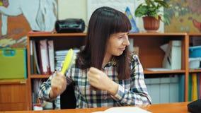 Ένας νέος θηλυκός δάσκαλος κτενίζει τη σκοτεινή τρίχα της, καθμένος στο γραφείο απόθεμα βίντεο