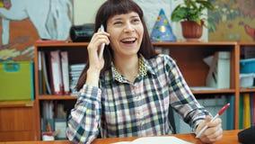 Ένας νέος θηλυκός δάσκαλος που μιλά στο τηλέφωνο στο γραφείο φιλμ μικρού μήκους