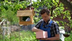 Ένας νέος κηπουρός στις μπλε φόρμες που ταΐζει τα πουλιά φιλμ μικρού μήκους