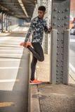 Ένας νέος μαύρος τεντώνει για να προετοιμαστεί για ένα τρέξιμο Στοκ Εικόνα