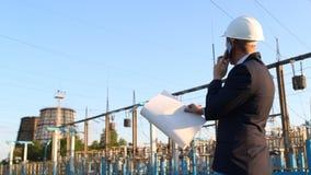 Ένας νέος μηχανικός εξετάζει το διάγραμμα σχεδίων σε ένα κλίμα εγκαταστάσεων παραγωγής ενέργειας και μιλά στο τηλέφωνο απόθεμα βίντεο