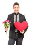 Ένας νέος μοντέρνος τύπος που κρατά μια δέσμη των λουλουδιών και της καρδιάς Στοκ Εικόνα
