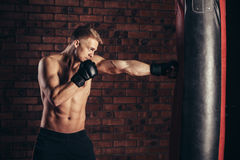 Ένας νέος μπόξερ στα μαύρα γάντια με έναν γυμνό κορμό επιλύει τις απεργίες punching στην τσάντα Στοκ εικόνα με δικαίωμα ελεύθερης χρήσης
