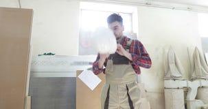 Ένας νέος ξυλουργός στη joinery ομοιόμορφη τοποθέτηση σε ένα άσπρο κράνος στο κεφάλι στην παραγωγή ξυλουργικής απόθεμα βίντεο