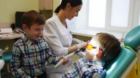 Ένας νέος οδοντίατρος γυναικών προετοιμάζει τα εργαλεία για την οδοντική επεξεργασία Υπομονετική συνεδρίαση αγοριών σε μια καρέκλ απόθεμα βίντεο