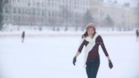 Ένας νέος πάγος γυναικών που κάνει πατινάζ έξω Βλέπει το φίλο της, που κυματίζει σε τους με ένα χέρι, σαλάχι πιό κοντά στη κάμερα απόθεμα βίντεο