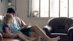 Ένας νέος πατέρας και η ευτυχής μικρή ξανθή κόρη του διαβάζουν μια ιστορία σχετικά με τον καναπέ δέρματος στη τραπεζαρία 4K απόθεμα βίντεο