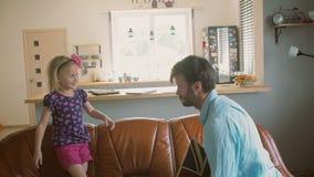 Ένας νέος πατέρας και η χαριτωμένη ευτυχής μικρή κόρη του που έχουν την πάλη μαξιλαριών στον καναπέ Σε αργή κίνηση, πυροβολισμός  απόθεμα βίντεο