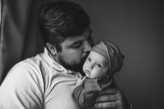 Ένας νέος πατέρας φιλά τη νεογέννητη κόρη του Πατέρας και νεογέννητη κινηματογράφηση σε πρώτο πλάνο μωρών στοκ εικόνα