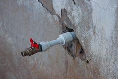 Ένας νέος πλαστικός σωλήνας με την κόκκινη στρόφιγγα που βγαίνει από τον παλαιό τοίχο Στοκ Φωτογραφίες