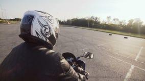 Ένας νέος ποδηλάτης σε ένα κράνος οδηγά στη μοτοσικλέτα του Κινηματογράφηση σε πρώτο πλάνο απόθεμα βίντεο