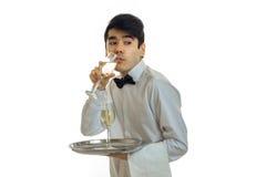 Ένας νέος σερβιτόρος σε ένα άσπρο πουκάμισο με μια πεταλούδα κρατά έναν δίσκο και μια σαμπάνια κατανάλωσης από ένα ποτήρι Στοκ Εικόνα