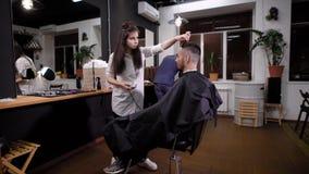 Ένας νέος στιλίστας γυναικών από την τρίχα τακτοποίησε τα κτυπήματα με trimmer για τον επισκέπτη barbershop, πελάτες του σαλονιού απόθεμα βίντεο