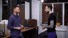 Ένας νέος στιλίστας τρίχας που εργάζεται σε ένα barbershop επικοινωνεί με τον πελάτη με έναν φιλικό τρόπο, ο οποίος έχει έρθει φιλμ μικρού μήκους