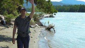Ένας νέος τουρίστας με ένα σακίδιο πλάτης που κυματίζει το χέρι του απόθεμα βίντεο