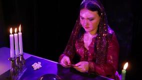 Ένας νέος τσιγγάνος με τα κεριά στις αντανακλάσεις οδηγεί τις κάρτες επάνω από τη σφαίρα καθρεφτών απόθεμα βίντεο