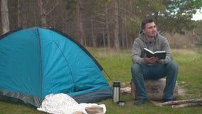 Ένας νέος τύπος κάθεται σε ένα μεγάλο κούτσουρο κοντά σε μια μπλε σκηνή και Temos στο δάσος και διαβάζει ένα βιβλίο απόθεμα βίντεο