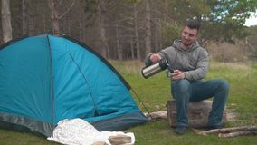 Ένας νέος τύπος κάθεται σε ένα μεγάλο κούτσουρο κοντά σε μια μπλε σκηνή στο δάσος και χύνεται το τσάι από thermos απόθεμα βίντεο