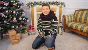 Ένας νέος τύπος κάθεται στο πάτωμα του σπιτιού του όπως η ανασκόπηση είναι μπορεί θέμα απεικόνισης Χριστουγέννων χρησιμοποιούμενο Στοκ Φωτογραφία
