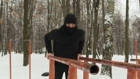 Ένας νέος τύπος μαύρο sportswear με μια κουκούλα και Balaclava ninja που εκτελούν τις ασκήσεις στους φραγμούς έναν χειμώνα χιονισ απόθεμα βίντεο