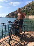 Ένας νέος τύπος με ένα σακίδιο πλάτης ταξιδεύει με το ποδήλατο θαλασσίως Seasc Στοκ Φωτογραφία
