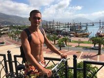 Ένας νέος τύπος με ένα σακίδιο πλάτης ταξιδεύει με το ποδήλατο θαλασσίως Seasc Στοκ Φωτογραφίες