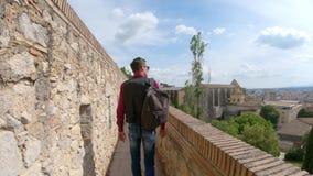 Ένας νέος τύπος με ένα σακίδιο πλάτης, ένας τουρίστας, περπατά κατά μήκος του τοίχου φρουρίων Girona, Ισπανία Τοίχος φρουρίων στι απόθεμα βίντεο