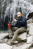 Ένας νέος τύπος πίνει το τσάι ή τον καφέ από thermos, καθμένος στις πέτρες κοντά σε έναν καταρράκτη στοκ εικόνες με δικαίωμα ελεύθερης χρήσης