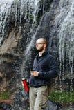 Ένας νέος τύπος πίνει το τσάι ή τον καφέ από thermos, στεμένος κοντά σε έναν καταρράκτη στα βουνά στοκ εικόνες