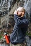 Ένας νέος τύπος πίνει το τσάι ή τον καφέ από thermos, στεμένος κοντά σε έναν καταρράκτη στα βουνά στοκ φωτογραφία με δικαίωμα ελεύθερης χρήσης