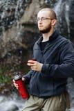 Ένας νέος τύπος πίνει το τσάι ή τον καφέ από thermos, στεμένος κοντά σε έναν καταρράκτη στα βουνά στοκ εικόνα