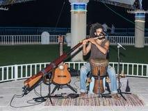Ένας νέος τύπος παίζει ένα φλάουτο το βράδυ στην προκυμαία στην πόλη Nahariya, στο Ισραήλ στοκ φωτογραφία