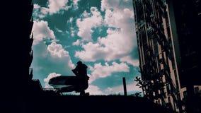 Ένας νέος τύπος περιβάλλει στα όπλα αγαπημένου του στο υπόβαθρο, stunningly όμορφα σύννεφα απόθεμα βίντεο
