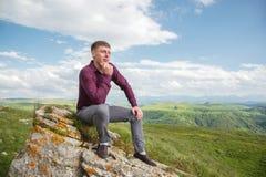 Ένας νέος τύπος που ντύνεται clasically κάθεται σε έναν βράχο στη φύση απολαμβάνοντας τη θέα Στοκ φωτογραφία με δικαίωμα ελεύθερης χρήσης