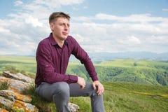 Ένας νέος τύπος που ντύνεται clasically κάθεται σε έναν βράχο στη φύση απολαμβάνοντας τη θέα Στοκ Φωτογραφίες