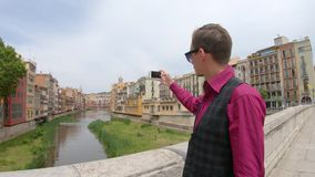 Ένας νέος τύπος πυροβολεί ένα βίντεο με ένα smartphone κοντά στον ποταμό Onyar Girona, Ισπανία απόθεμα βίντεο