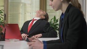 Ένας νέος τύπος σε ένα κοστούμι φλερτάρει με ένα κορίτσι στο γραφείο, ουρλιάζει όπως έναν λύκο, έννοια χιούμορ Απασχομένος στο γρ φιλμ μικρού μήκους