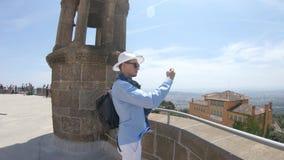 Ένας νέος τύπος σε ένα μαντίλι και ένα καπέλο πυροβολεί ένα βίντεο με ένα smartphone κοντά στο ναό της ιερής καρδιάς στο υποστήρι απόθεμα βίντεο