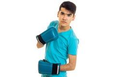 Ένας νέος τύπος σε ένα μπλε πουκάμισο και εγκιβωτίζοντας γάντια φαίνεται κεκλεισμένων των θυρών Στοκ Φωτογραφίες