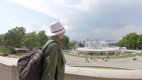 Ένας νέος τύπος, ένας τουρίστας στα γυαλιά στέκεται και χαμογελά κοντά στο τόξο φιλμ μικρού μήκους