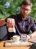 Ένας νέος τύπος χύνει μια κρέμα στον καφέ σε έναν καφέ στον πίνακα Στοκ εικόνα με δικαίωμα ελεύθερης χρήσης