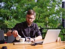 Ένας νέος τύπος χύνει μια κρέμα στον καφέ σε έναν καφέ στον πίνακα στοκ εικόνες