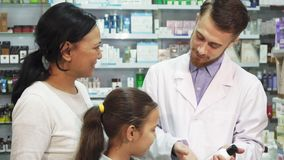 Ένας νέος φαρμακοποιός μιλά για ένα από τα προϊόντα φαρμακείων στους πελάτες του στοκ εικόνες
