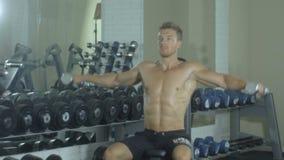 Ένας νέος όμορφος αθλητικός τύπος συμμετέχει ενεργά στις αθλητικές ασκήσεις γιατί παραδίδει την αίθουσα, εκπαιδευτικός δύο χέρια  φιλμ μικρού μήκους